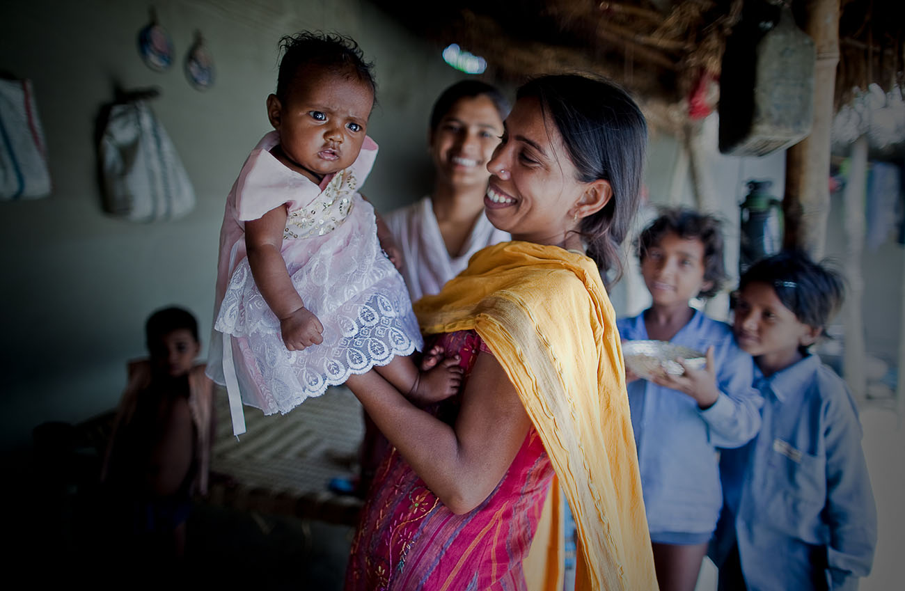 A proud Indian mother holds up her beautiful daughter.
