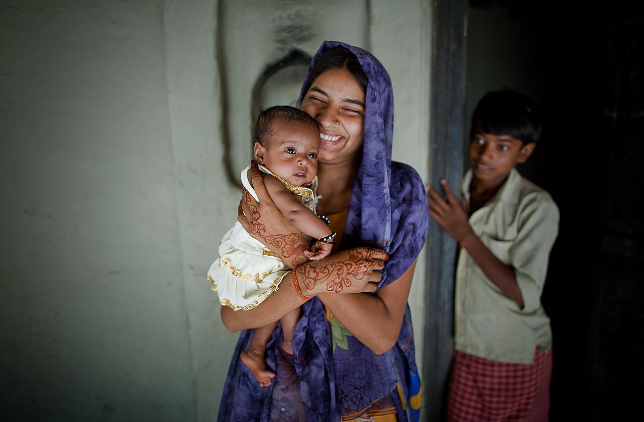 A mother in India smiles while she holds her baby.