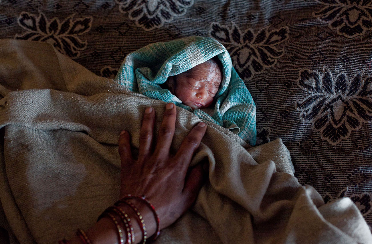 An tiny Indian baby sleeps soundly under blankets.