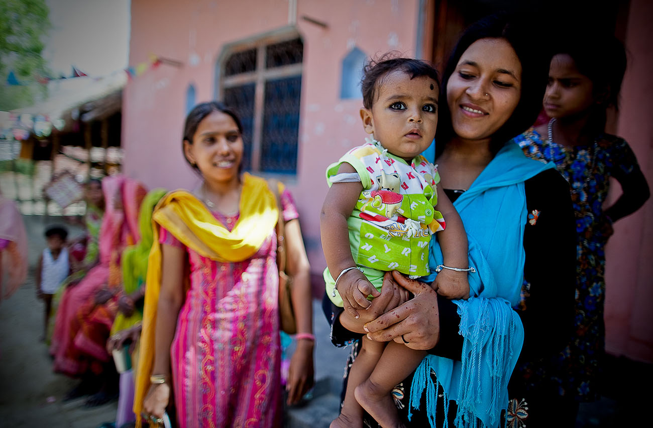 A baby in India held by her mother.