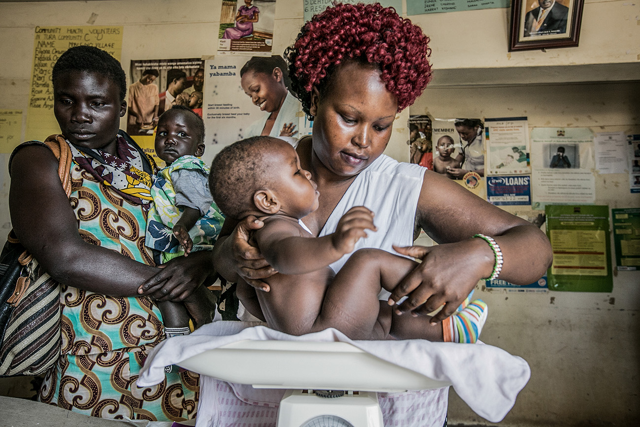 A mother and her infant daughter wait for their check up in a rural clinic in Kenya.