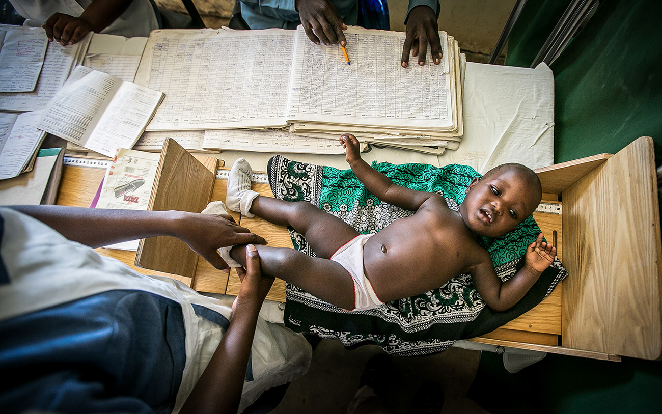 A child being measured during a check up in a clinic in rural Kenya.