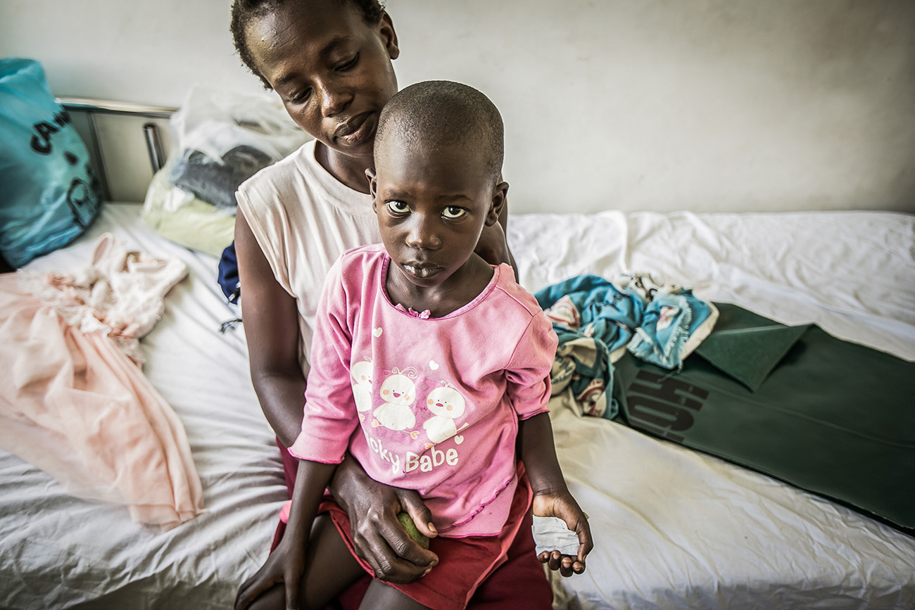 A mother and her child wait to be examined in a clinic in rural Kenya.