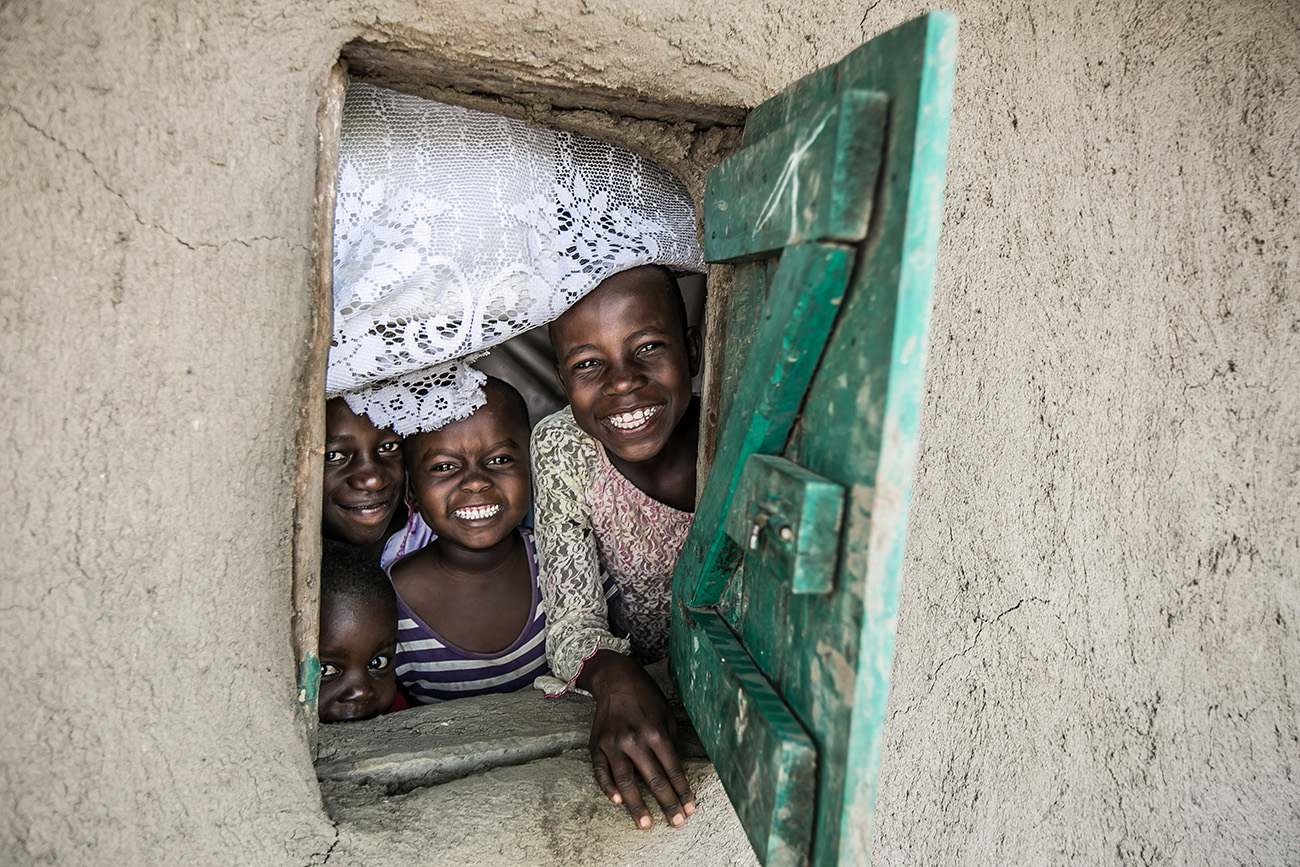 Village children peering out a window in Kenya.