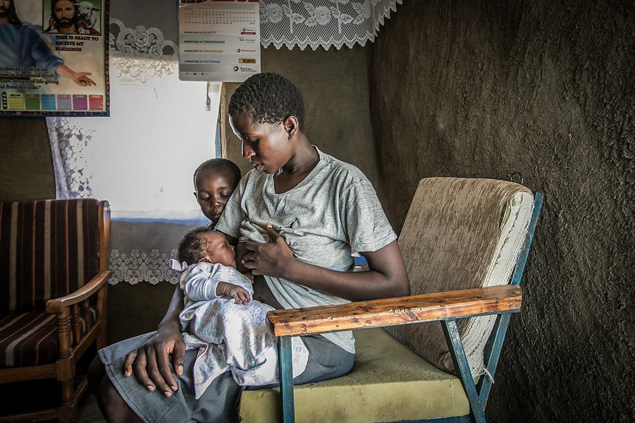 A woman breastfeeding her newborn in her home in a village in rural Kenya.