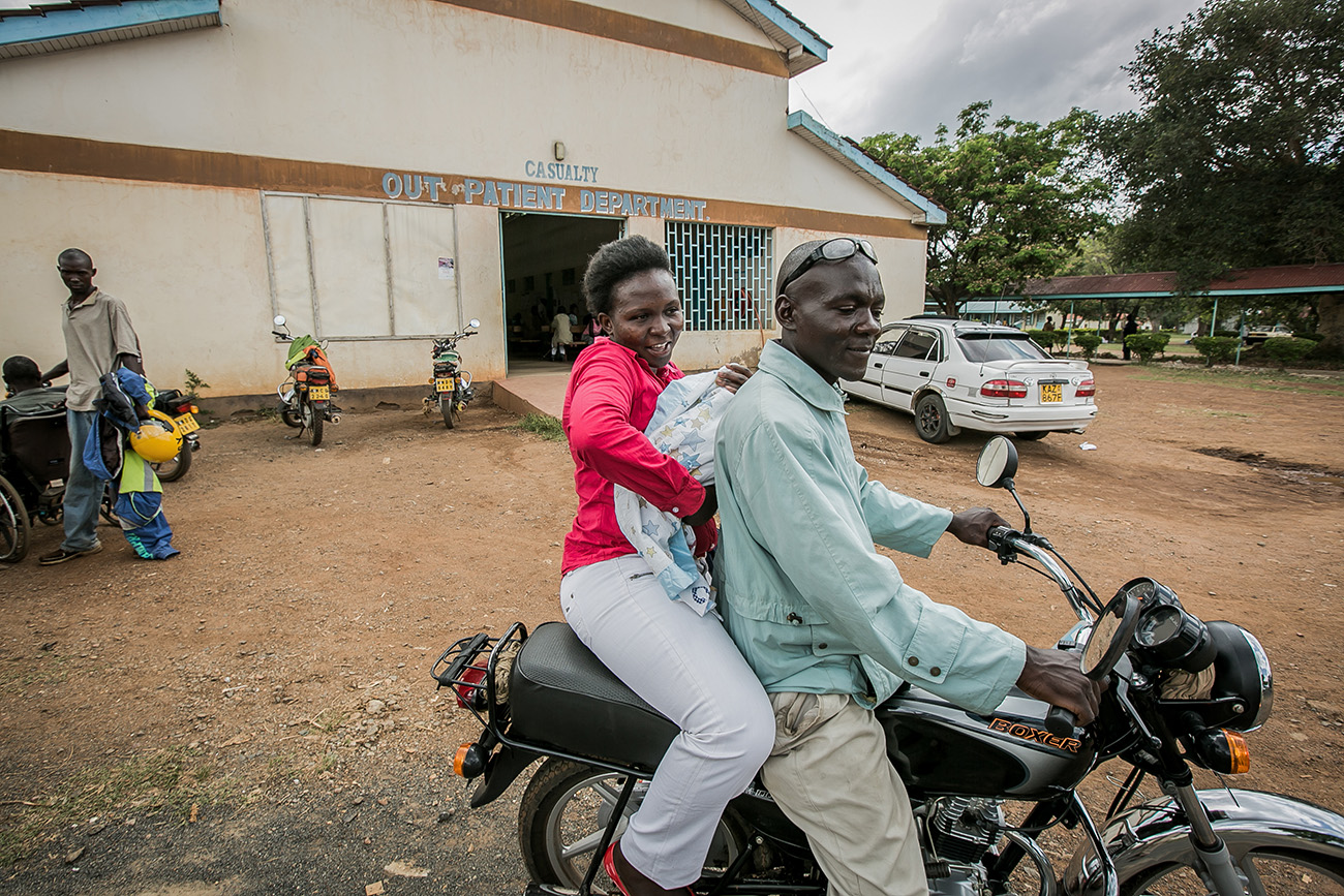 A mother takes her newborn home on a motorcycle after giving birth in a rural clinic in Kenya.