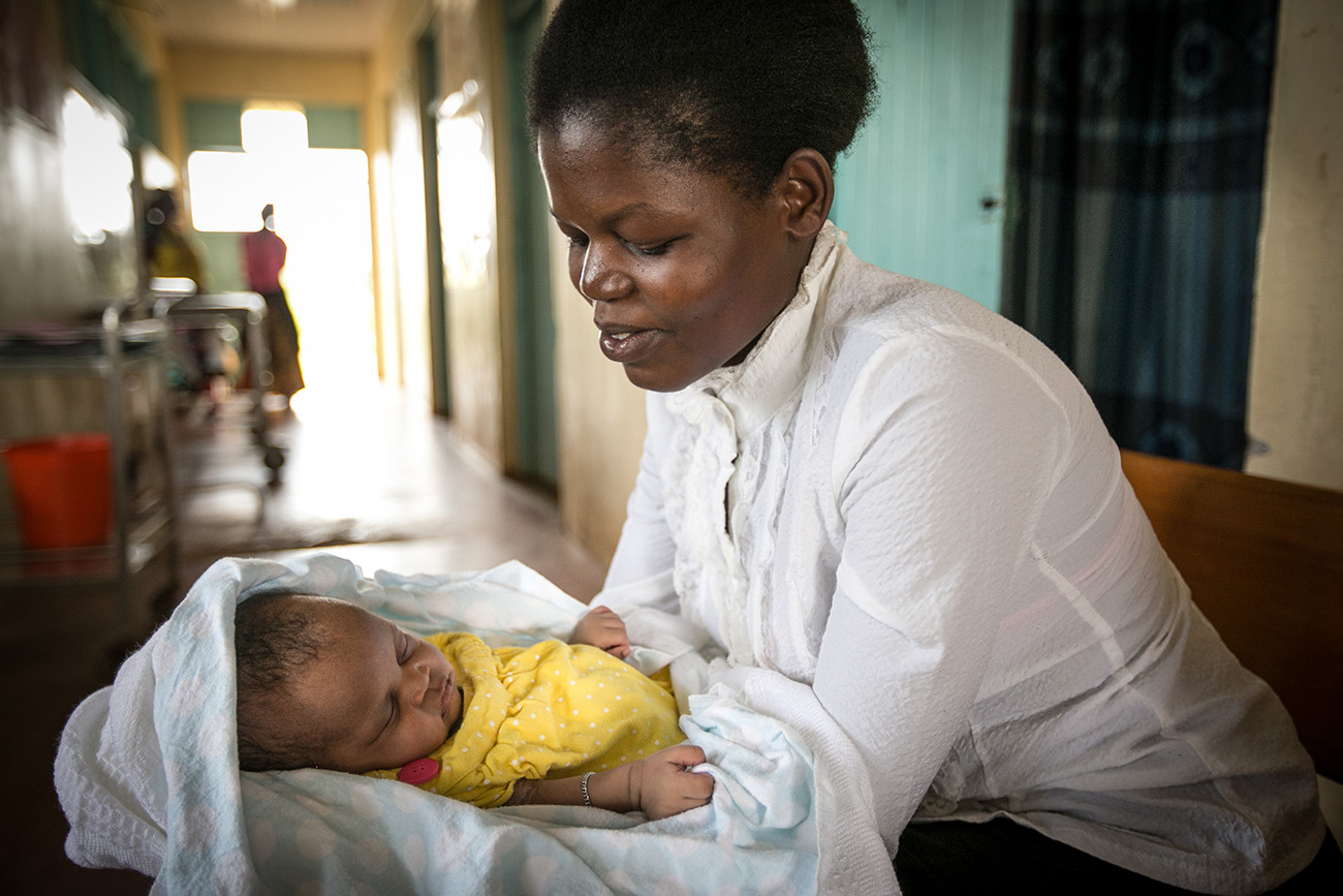 a mother holds her newborn in the maternal ward of a clinic in rural Kenya.