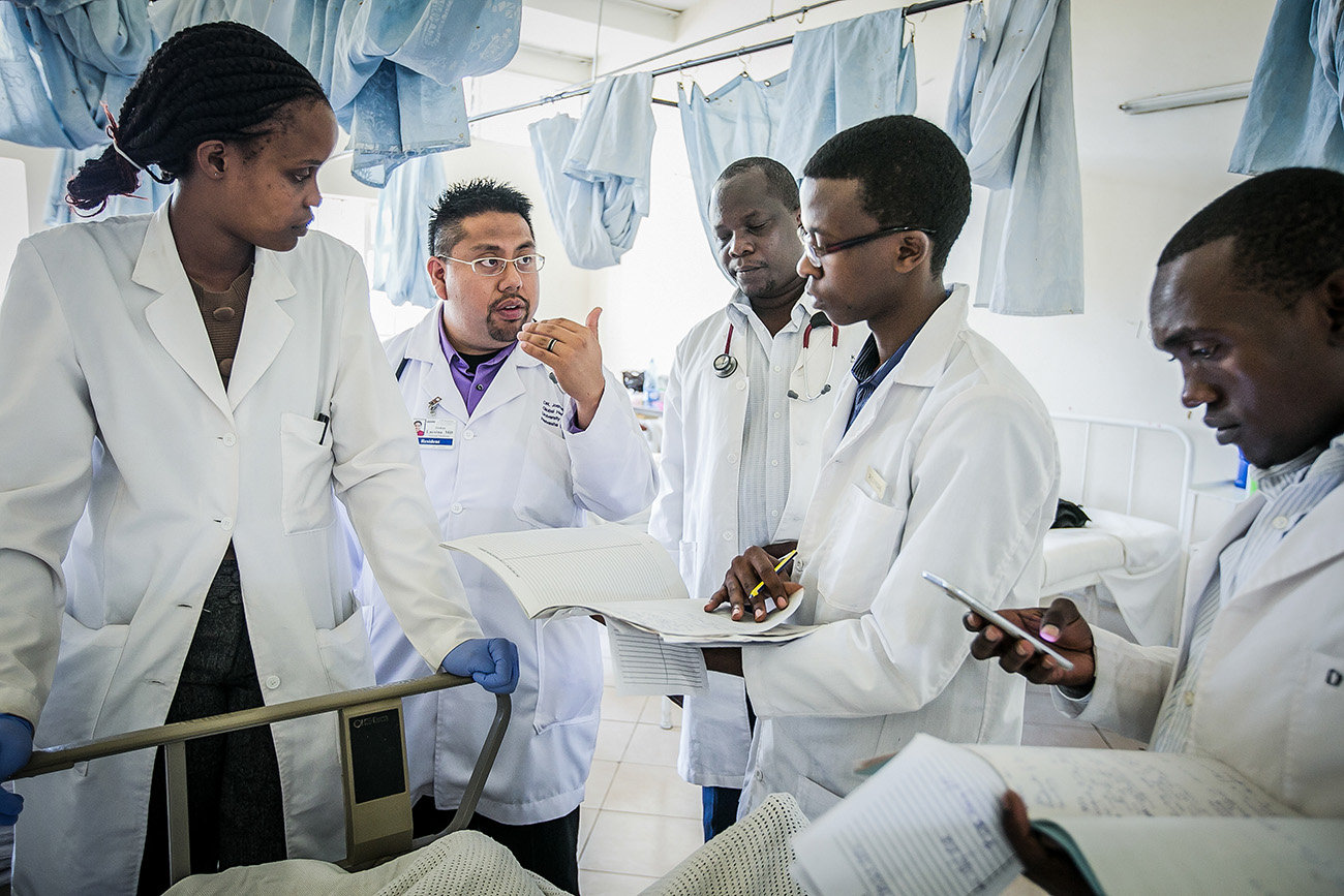 Medical students from Kenya looking over charts with doctors and medical residents.