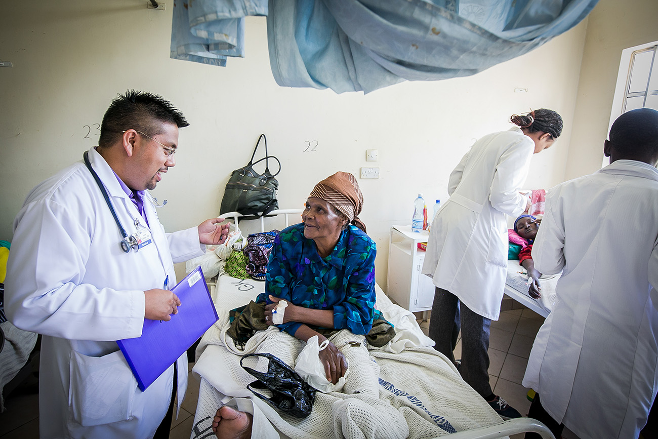 Medical professional speaking with elderly patient in hospital bed in Kenyan Hospital.