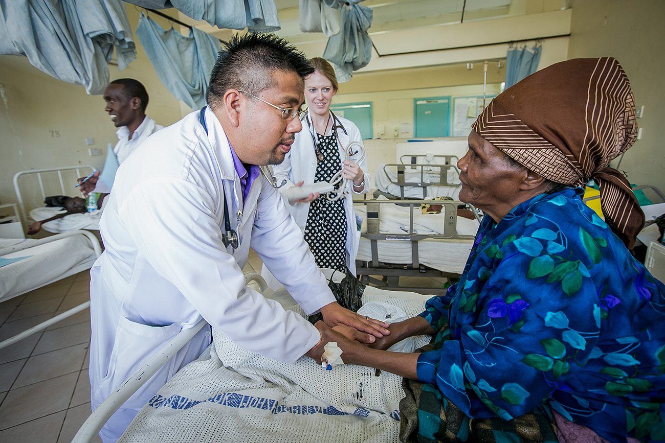 A medical professional speaking with a patient in a hospital bed in Kenya.