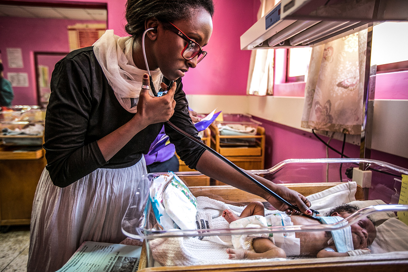 A medical school resident examine a newborn infant in the maternal ward in the government hospital in Naivasha, Kenya.