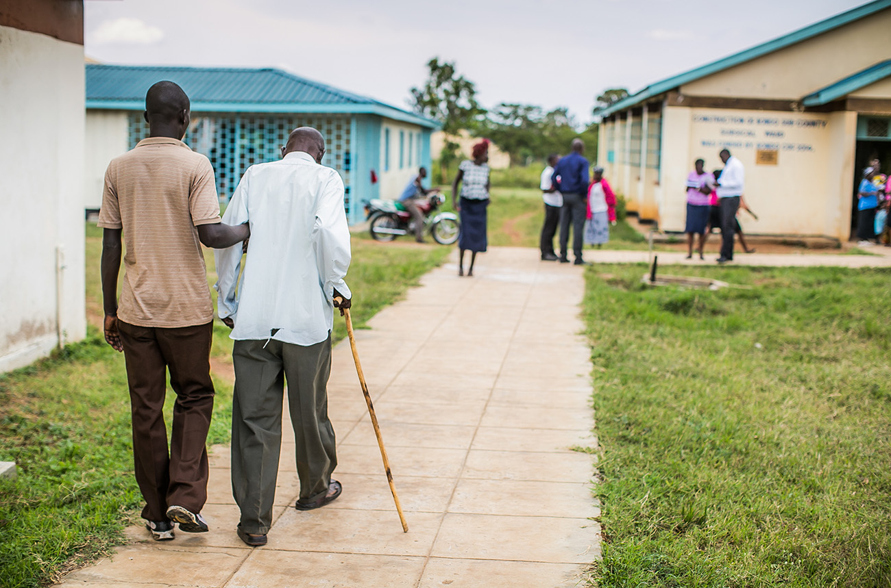 A son helps his father walk to a rural health clinic in Kenya.