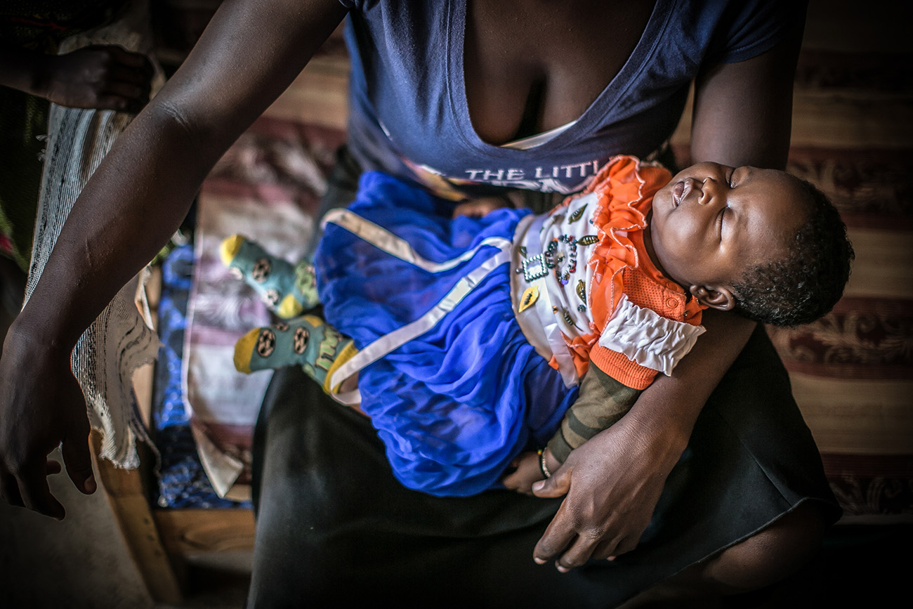 A mother holding her infant daughter in their home in a village in rural Kenya.